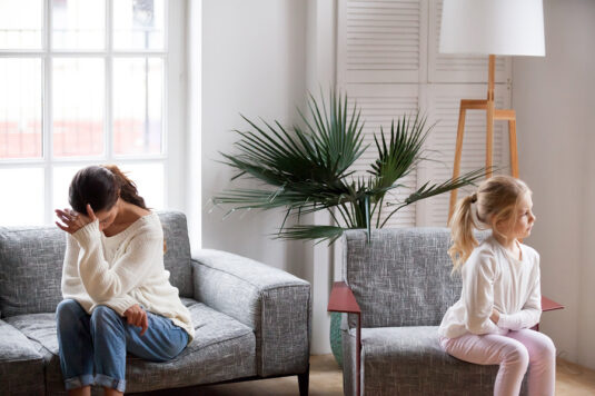 Sad tired mother and sulky angry offended child girl not talking after conflict in living room, stubborn kid daughter pouting ignoring depressed mother upset by argument, family conflict concept